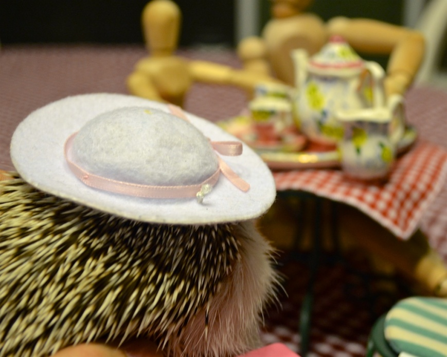 Hedgehog, hear turned away, wearing hat at tea party.
